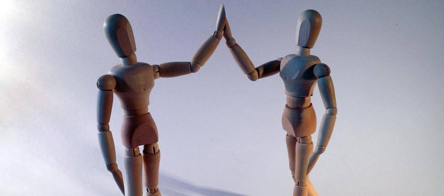 Burnoutprävention im Unternehmen zwei Puppen klatschen ein